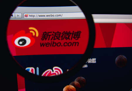 LISBON, PORTUGAL - FEBRUARY 21, 2014: Photo of Sina Weibo homepage on a monitor screen through a magnifying glass.