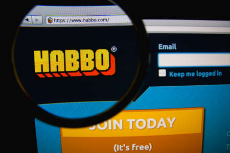 LISBON, PORTUGAL - FEBRUARY 21, 2014: Habbo homepage on a monitor screen through a magnifying glass. Редакционное