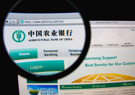 financial service: LISBON, PORTUGAL - FEBRUARY 21, 2014: Photo of Agricultural Bank of China homepage on a monitor screen through a magnifying glass.