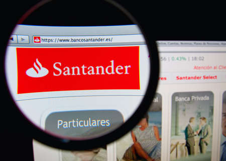 LISBON, PORTUGAL - FEBRUARY 21, 2014: Photo of the Santander Group homepage on a monitor screen through a magnifying glass.
