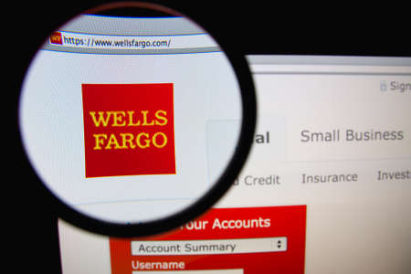 LISBON, PORTUGAL - FEBRUARY 21, 2014: Photo of Wells Fargo homepage on a monitor screen through a magnifying glass.