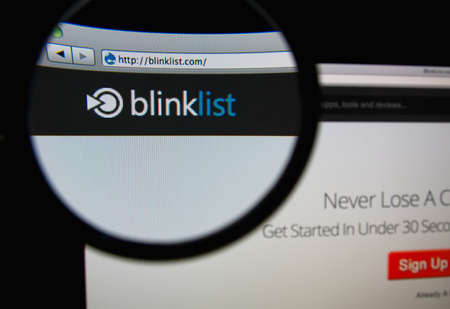 bookmarking: LISBON, PORTUGAL - MARCH 7, 2014: Photo of Blinklist homepage on a monitor screen through a magnifying glass.
