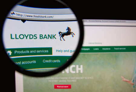 lloyd's: LISBON, PORTUGAL - MARCH 7, 2014: Photo of Lloyds Bank homepage on a monitor screen through a magnifying glass.