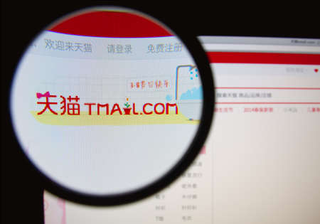 LISBON, PORTUGAL - MARCH 10, 2014: Photo of Tmall.com homepage on a monitor screen through a magnifying glass. Редакционное