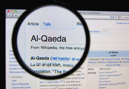 wikipedia: LISBON, PORTUGAL - MARCH 13, 2014: Photo of Wikipedia article page about Al-Qaeda on a monitor screen through a magnifying glass.