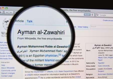 wikipedia: LISBON, PORTUGAL - APRIL 1, 2014: Photo of Wikipedia article page about Ayman al-Zawahiri on a monitor screen through a magnifying glass.