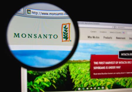 LISBON, PORTUGAL - APRIL 1, 2014: Photo of Monsanto homepage on a monitor screen through a magnifying glass. Редакционное