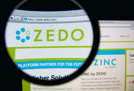 the publisher: LISBON, PORTUGAL - MARCH 10, 2014: Photo of Zedo homepage on a monitor screen through a magnifying glass. Editorial