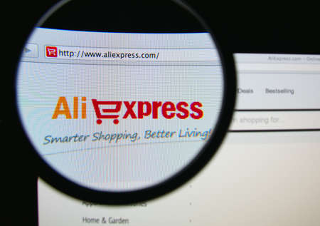 LISBON, PORTUGAL - MARCH 10, 2014: Photo of the AliExpress homepage on a monitor screen through a magnifying glass.