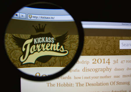 torrent: LISBON, PORTUGAL - MARCH 10, 2014: Photo of KickassTorrents homepage on a monitor screen through a magnifying glass.
