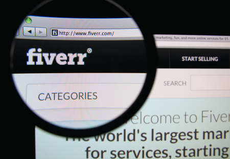 LISBON, PORTUGAL - MARCH 10, 2014: Photo of Fiverr homepage on a monitor screen through a magnifying glass. 報道画像