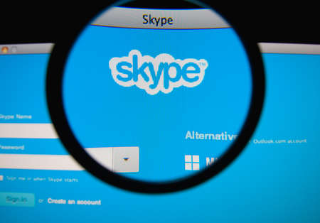 LISBON, PORTUGAL - MARCH 10, 2014: Photo of Skype homepage on a monitor screen through a magnifying glass.