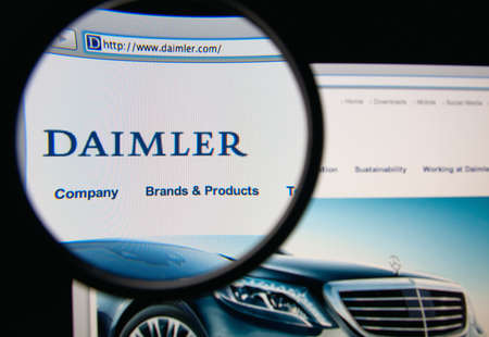 ag: LISBON, PORTUGAL - MARCH 10, 2014: Photo of Daimler AG homepage on a monitor screen through a magnifying glass.