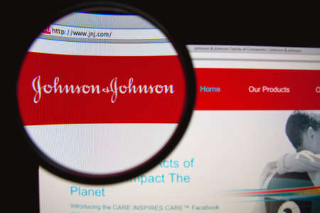 LISBON, PORTUGAL - MARCH 10, 2014: Photo of Johnson & Johnson homepage on a monitor screen through a magnifying glass.