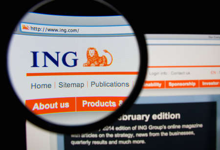 ing: LISBON, PORTUGAL - MARCH 10, 2014: Photo of the ING Group homepage on a monitor screen through a magnifying glass.