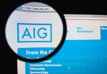 LISBON, PORTUGAL - MARCH 10, 2014: Photo of American International Group (AIG) homepage on a monitor screen through a magnifying glass. Редакционное