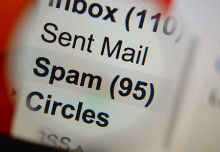 deletion: Magnifying glass showing a spam folder in the mailbox on the monitor screen.