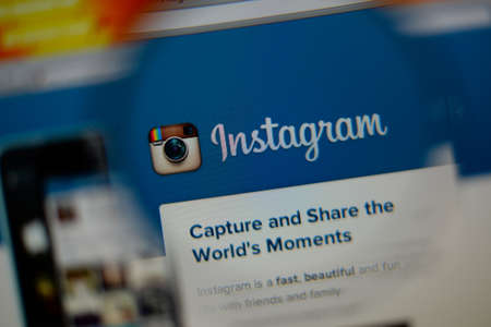 LISBON, PORTUGAL - AUGUST 3, 2014: Photo of Instagram homepage on a monitor screen through a magnifying glass. 報道画像