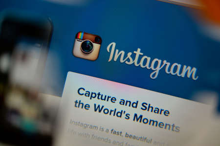 LISBON, PORTUGAL - AUGUST 3, 2014: Photo of Instagram homepage on a monitor screen through a magnifying glass. Редакционное