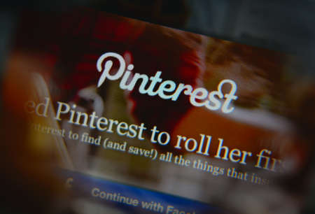 pinterest: LISBON, PORTUGAL - AUGUST 3, 2014: Photo of Pinterest homepage on a monitor screen through a magnifying glass.
