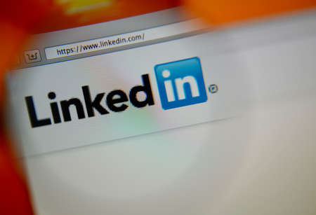 LISBON, PORTUGAL - AUGUST 3, 2014: Photo of LinkedIn homepage on a monitor screen through a magnifying glass. 報道画像