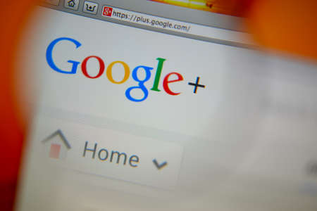 google: LISBON, PORTUGAL - AUGUST 3, 2014: Photo of Google+ homepage on a monitor screen through a magnifying glass.