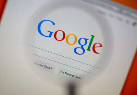 google: LISBON, PORTUGAL - AUGUST 3, 2014: Photo of Google homepage on a monitor screen through a magnifying glass.