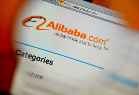 alibaba: LISBON, PORTUGAL - FEBRUARY 17, 2014: Alibaba homepage on a monitor screen through a magnifying glass.