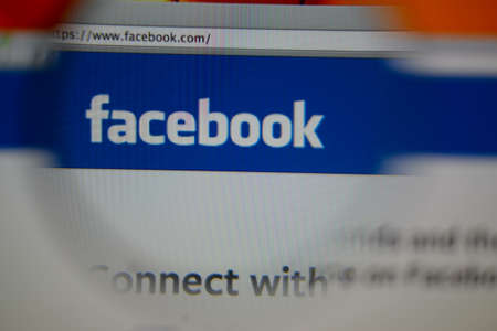 LISBON, PORTUGAL - AUGUST 3, 2014: Photo of Facebook homepage on a monitor screen through a magnifying glass.