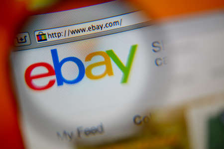ebay: LISBON, PORTUGAL - AUGUST 3, 2014: Photo of Ebay homepage on a monitor screen through a magnifying glass.