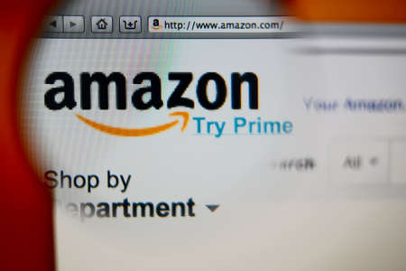 LISBON, PORTUGAL - AUGUST 3, 2014: Photo of Amazon homepage on a monitor screen through a magnifying glass.