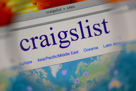 LISBON, PORTUGAL - FEBRUARY 21, 2014: Photo of Craigslist homepage on a monitor screen through a magnifying glass.