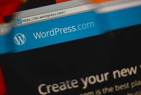 LISBON, PORTUGAL - MARCH 10, 2014: Photo of WordPress.com homepage on a monitor screen through a magnifying glass.