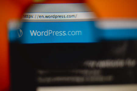 LISBON, PORTUGAL - AUGUST 3, 2014: Photo of WordPress.com homepage on a monitor screen through a magnifying glass. Редакционное