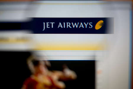 airways: LISBON, PORTUGAL - AUGUST 27, 2014: Photo of Jet Airways homepage on a monitor screen through a magnifying glass.
