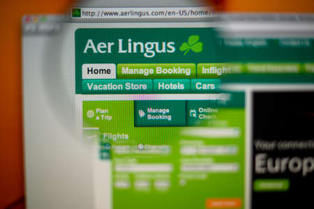 LISBON, PORTUGAL - AUGUST 27, 2014: Photo of Aer Lingus homepage on a monitor screen through a magnifying glass.