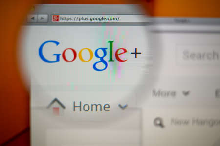 google plus: LISBON, PORTUGAL - AUGUST 3, 2014: Photo of Google+ homepage on a monitor screen through a magnifying glass.