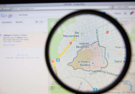 LISBON, PORTUGAL - MARCH 13, 2014: Photo of Google Maps pinpointing the Vatican City State on a monitor screen through a magnifying glass.