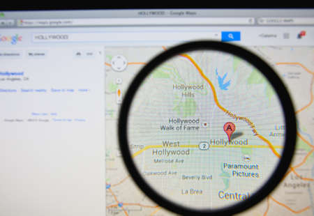 LISBON, PORTUGAL - MARCH 13, 2014: Photo of Google Maps pinpointing Hollywood on a monitor screen through a magnifying glass.