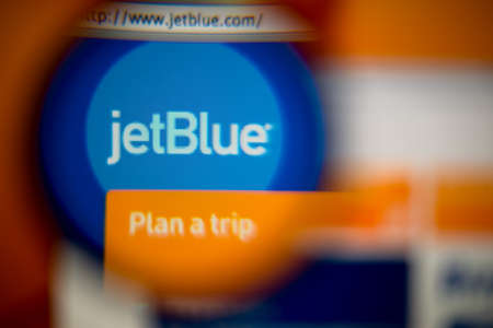 jetblue: LISBON, PORTUGAL - AUGUST 27, 2014: Photo of JetBlue Airways homepage on a monitor screen through a magnifying glass. Editoriali