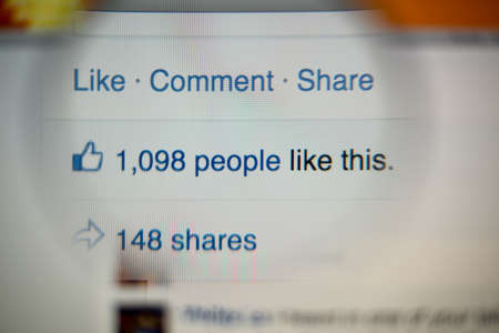comments: LISBON, PORTUGAL - AUGUST 27, 2014: Photo of Facebook notifications of Likes and Shares on a monitor screen through a magnifying glass.