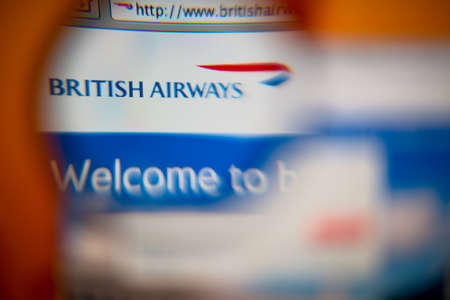 airways: LISBON, PORTUGAL - AUGUST 27, 2014: Photo of British Airways homepage on a monitor screen through a magnifying glass. Editorial