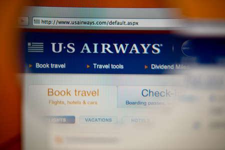american airlines: LISBON, PORTUGAL - AUGUST 27, 2014: Photo of US Airways homepage on a monitor screen through a magnifying glass.
