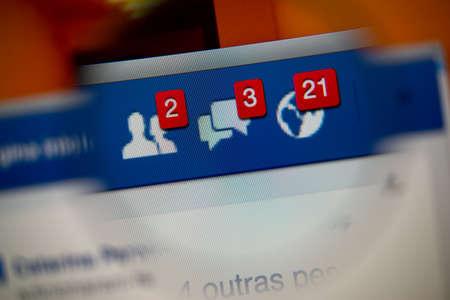 alerta: LISBOA, Portugal - 27 de agosto 2014: Foto de Facebook alertas de solicitudes de amistad, mensajes de la bandeja de entrada y las notificaciones en la pantalla del monitor a través de una lupa.