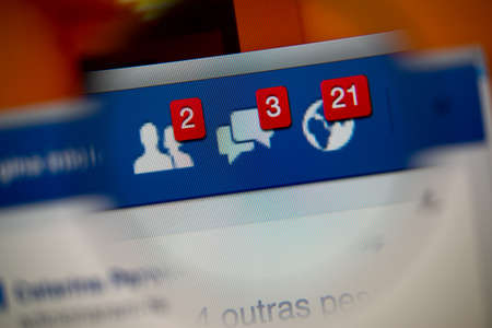 LISBON, PORTUGAL - AUGUST 27, 2014: Photo of Facebook alerts of friend requests, messages inbox and notifications on a monitor screen through a magnifying glass.