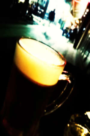 Blurred fresh unfiltered beer and blurred blured lighhts of urban street city