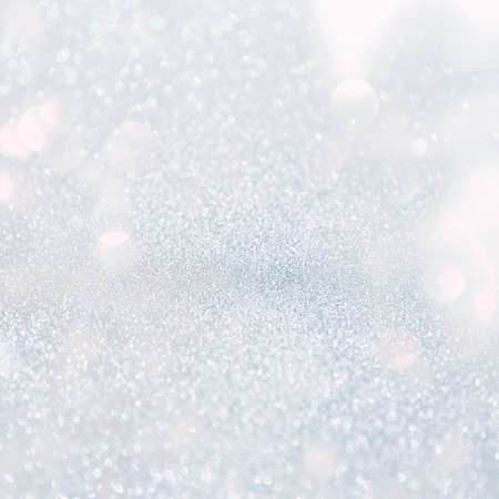 Silver white glittering Christmas lights. Blurred abstract grey background