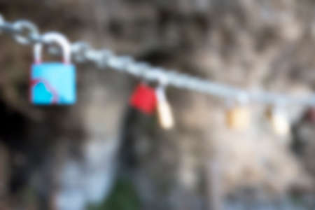 Blurred Many love padlocks locked on chain on a blurred background. Tourists place. Love sign and romance concept.