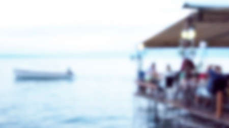 Blurred image of waterfront luxury restaurant and people at travel place with a boat sailing. Twilight blur holiday concept.