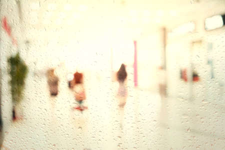 look at the shopping mall through the rain window. Blur store with bokeh background.  Business people walking in the office corridor. 免版税图像